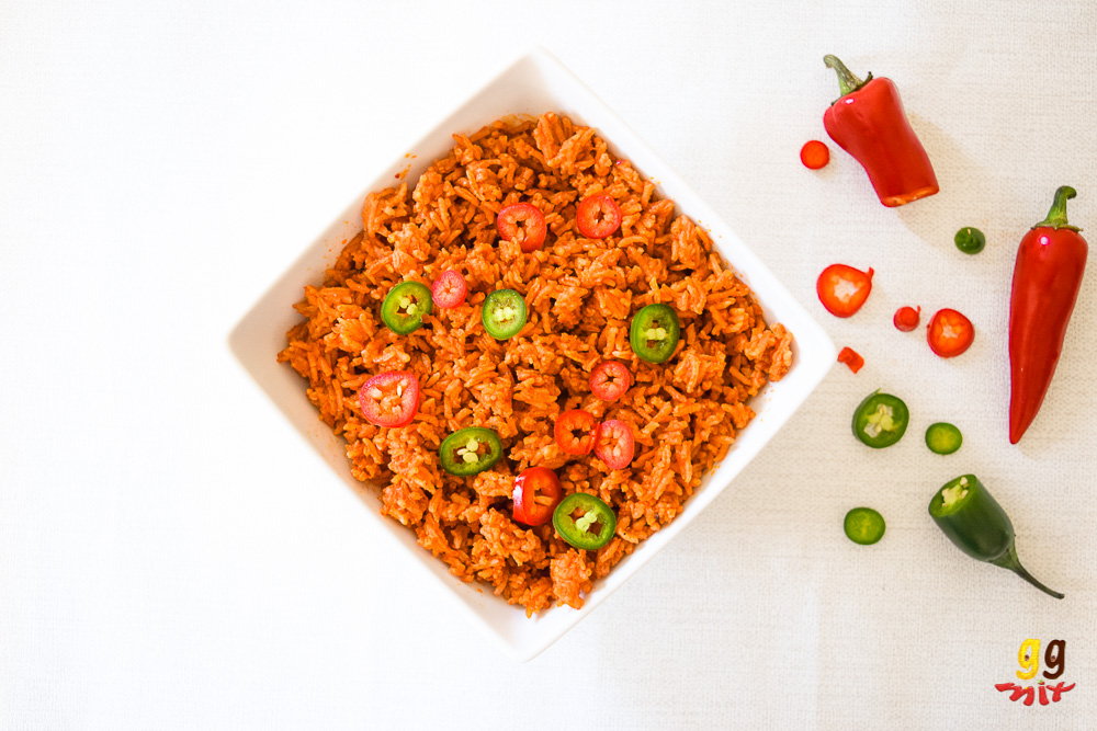ghanaian jollof rice in a bowl with sliced red and green chillies sprinkled on the top on the side are 1 1/2 red chillies, 1/2 a green chili and slices of red and green chilllies