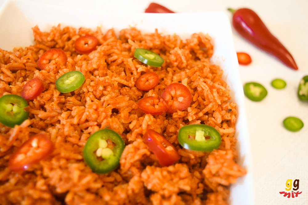 ghanaian jollof rice in a bowl with sliced red and green chillies sprinkled on the top. There's a whole red chilli and slices of red and green chillies in the background