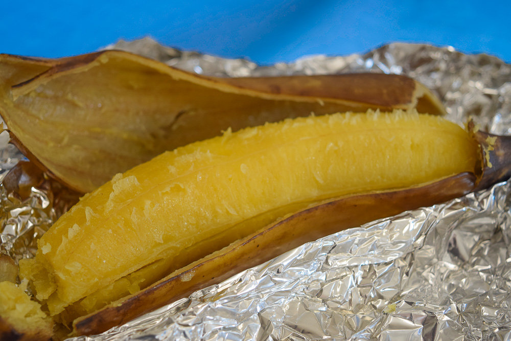 baked plantain still in its skin but half peeled sitting on foil