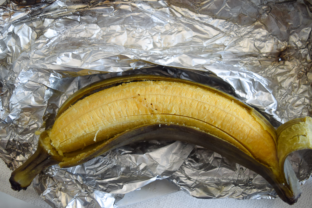 boiled plantain still in its skin with a piece of skin peeled off