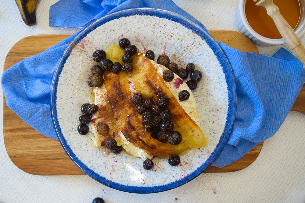 a bowl of fried plantain laied over some Greek yogurt with blueberries, cinnamon and honey drizzled on top.