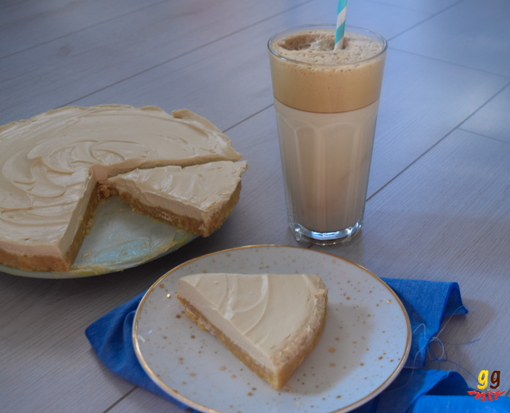 a greek frappe coffee cheesecake with 2 slices cut out and a glass of greek frappr coffee