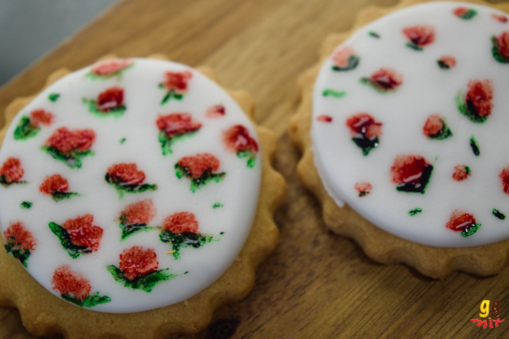 cookies covered with white fondant that has red roses with green leaves painted on it