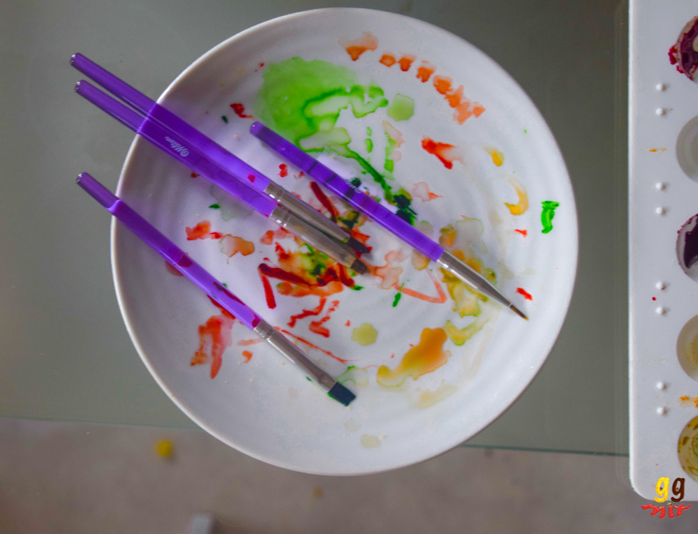 a plate with a rainbow of food colouring marks and 4 paint brushes across the plate