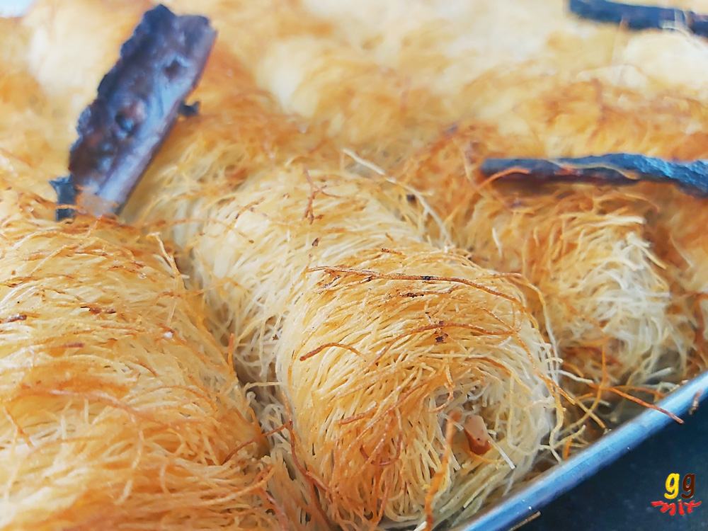 a tray of baked golden kataifi rolls with a few cinnamon sticks on top
