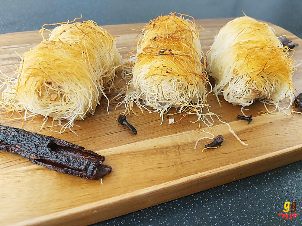 three kataifi rolls on a wooden board with a cinnamon stick three cloves on the board too