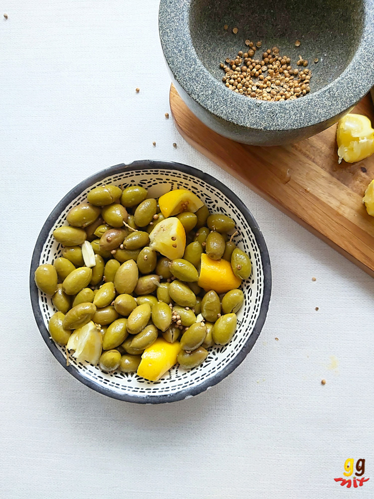 ELIES TSAKISTES GREEK CRACKED GREEN OLIVES IN A BOWL WITH PESTAL AND MORTAR