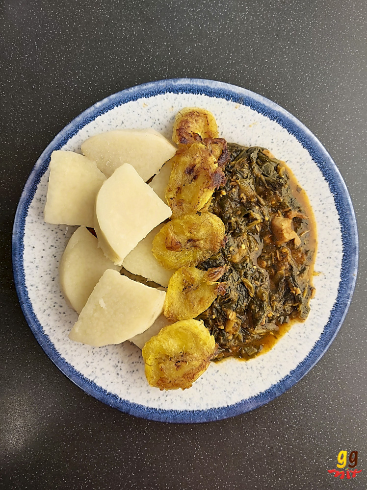 A PLATE OF PUNA YAM CHUNKS FRIED PLANTAIN AND KONTOMIRE GHANAIAN LAMB AND SPINACH STEW