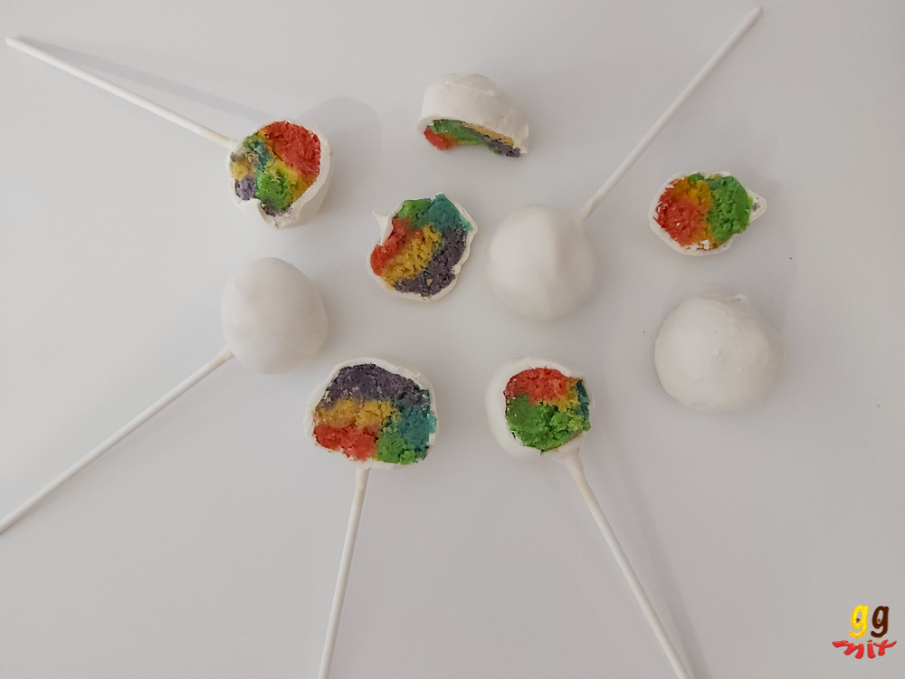 5 cake pops. 3 are in half and reveal a rainbow coloured center and 2 are still whole with a white chocolate coating plus half a rainbow truffle