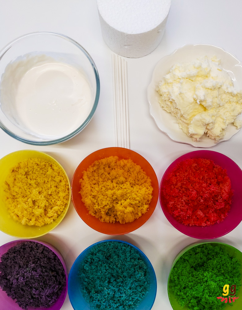 6 rainbow coloured bowls with matching coloured cake, red, orange, yellow, green, blue, purple. A bowl of white chocolate, a plate of vanilla buttercream, a pile of white cake pop sticks and a circular polystyrene block