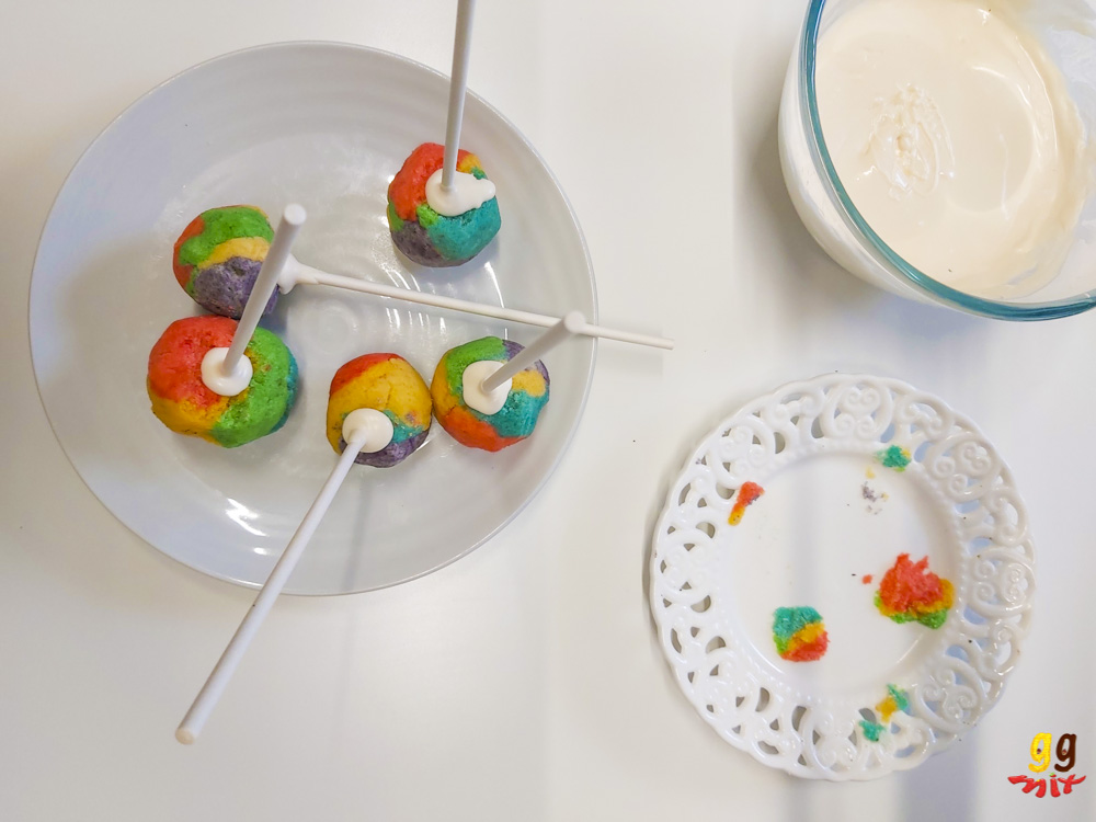 5 rainbow cake pops with sticks inserted and a chocolate seal, A plate with stuck on rainbow cake and a bowl of white chocolate