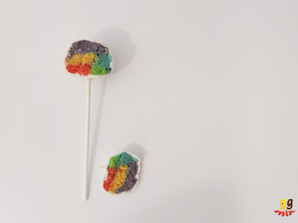 1 cake pop in half showing a rainbow coloured center
