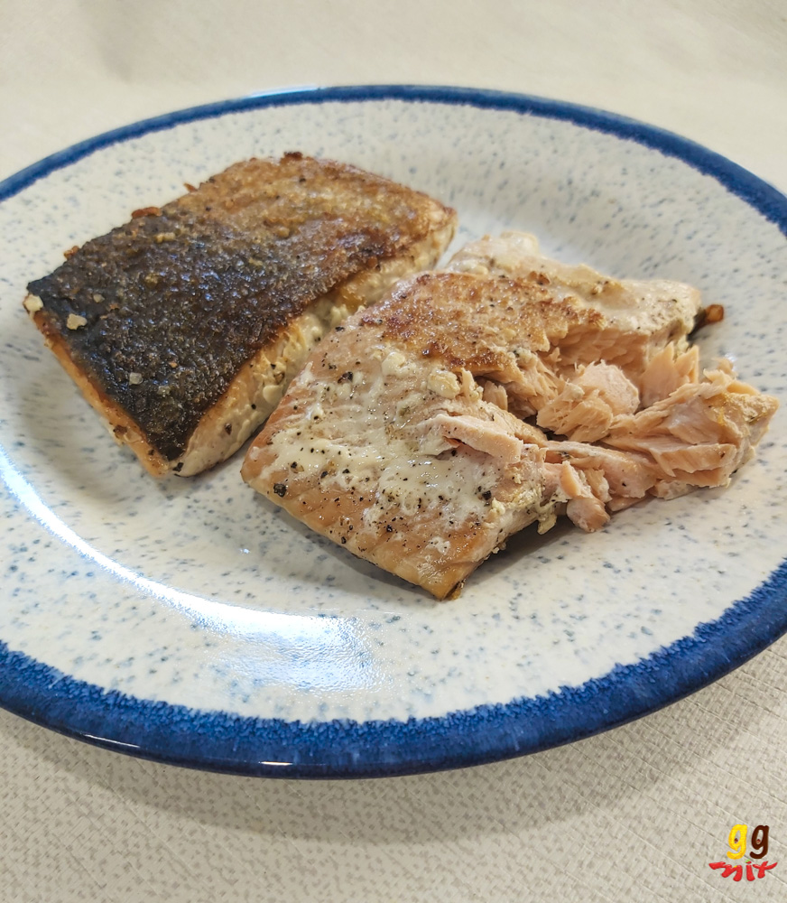 2 salmon fillets on a plate 1 fillet is upside down with a crispy skin and the other flesh side up and flakes of salmon falling apart