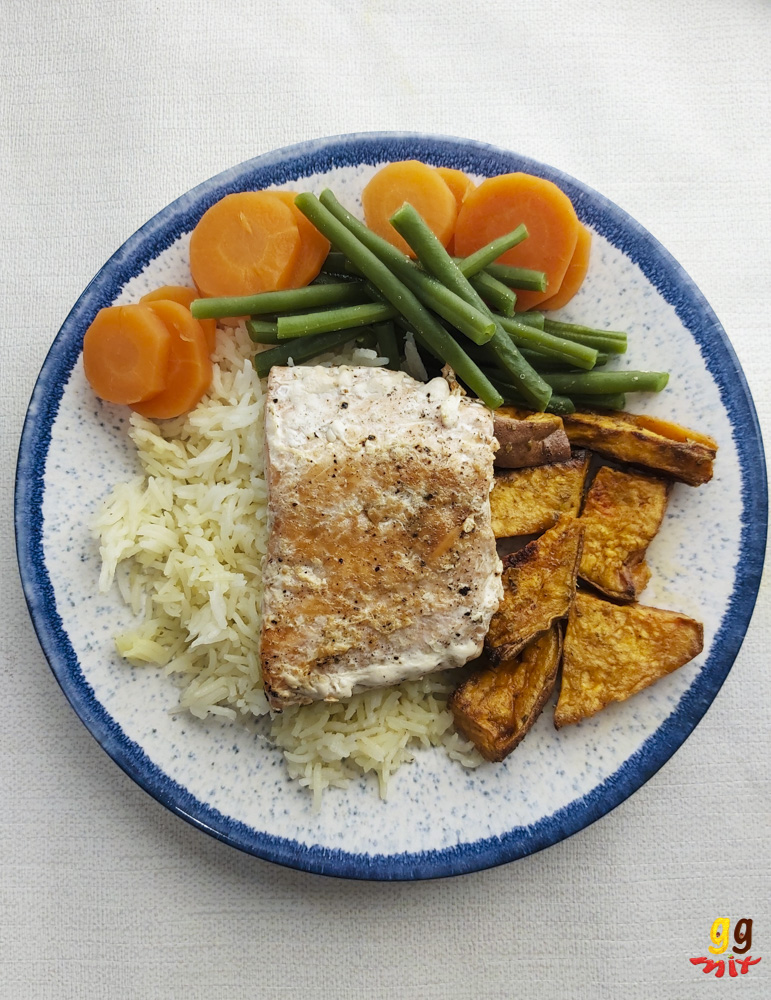 a plate with a salmon fillet sitting on some lemon rice, sweet potatoes, carrots and runner beans