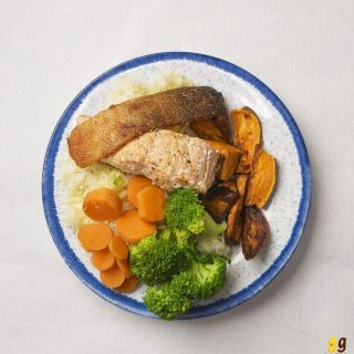 a plate with a salmon fillet and a crispy skin on top sitting on some lemon rice, sweet potatoes, carrots and broccoli