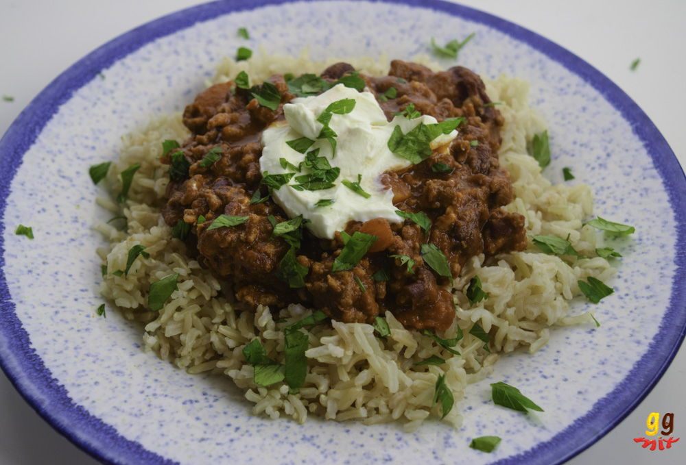 a plate of brown rice and chilli con carne topped with some Greek yogurt in the middle and a sprinkling of chopped parsley