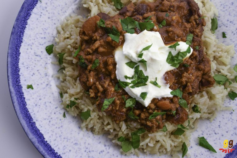 A PLATE OF BROWMN RICE WITH CHILLI CON CARNE ON TOP. tOPPED WITH SOME gREEK YOGURT AND A SPRINKLING OF PARSLEY