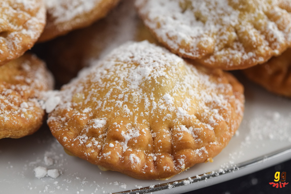 round bourekia me anari small hand pies dusted with icing sugar on a platter