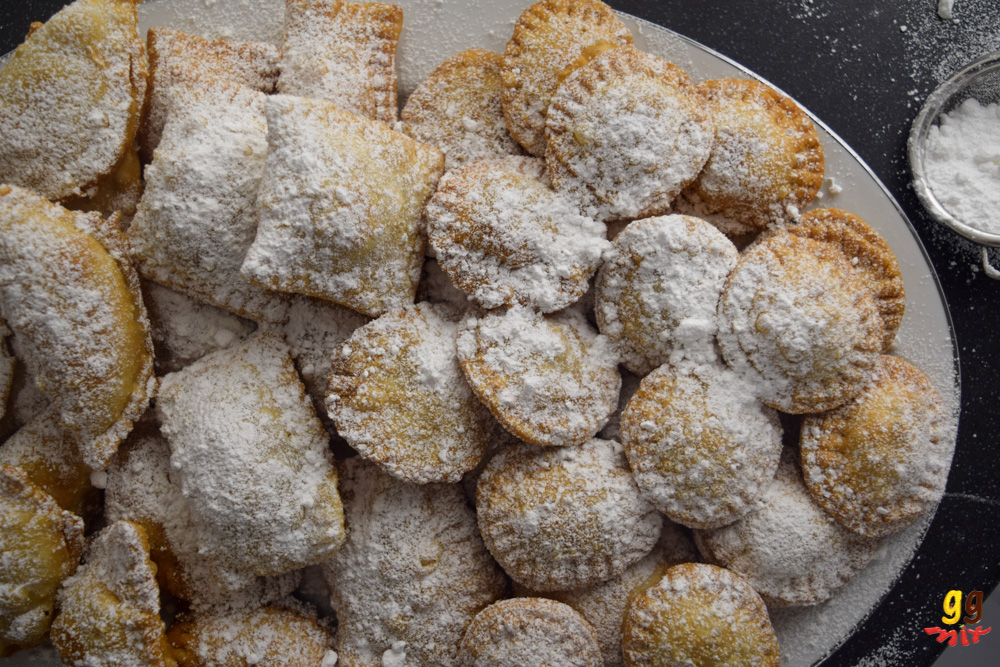 round, square, rectangular and crescent shaped bourekia me anari small hand pies dusted with icing sugar on a platter