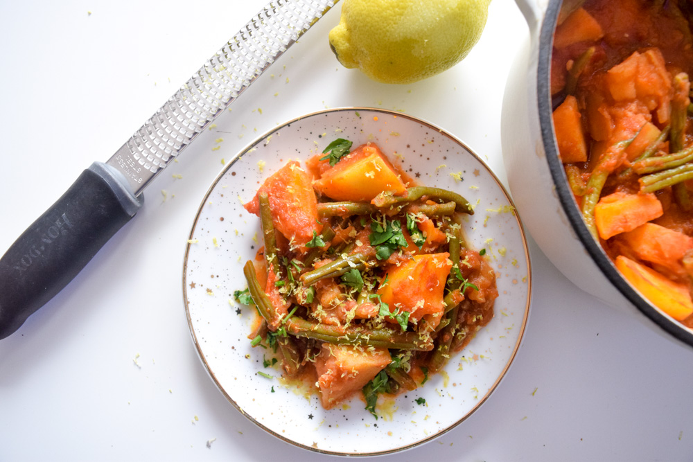 a plate of fasolakia green beans and potatoes in a tomatoe sauce topped with lemon zest and parsley