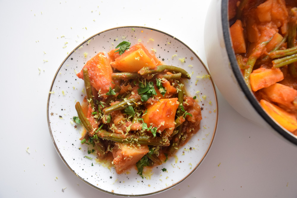 a plate and pot of fasolakia green beans and potatoes in a tomatoe sauce topped with lemon zest and parsley