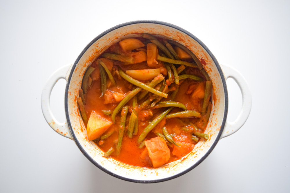a pot of fasolakia green beans and potatoes in a tomatoe sauce