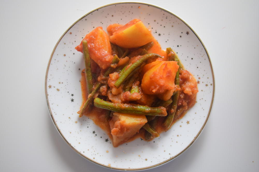 a plate of fasolakia green beans and potatoes in a tomatoe sauce