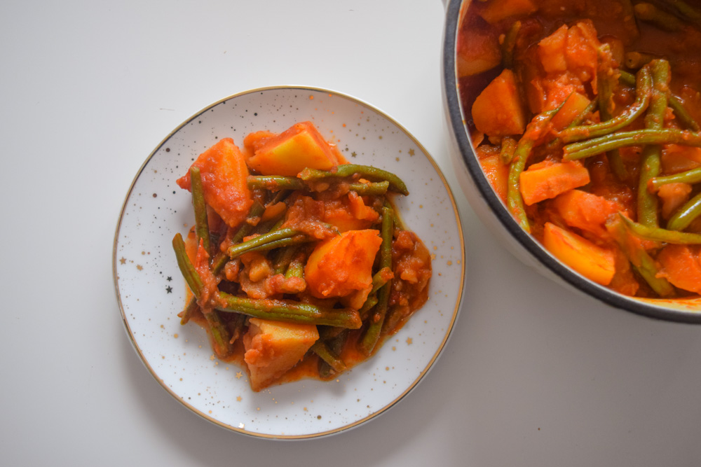 a plate and pot of fasolakia green beans and potatoes in a tomatoe sauce